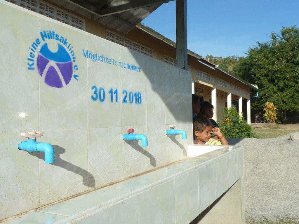 Langes Waschbecken mit mehreren Wasserhähnen an einer Wand.