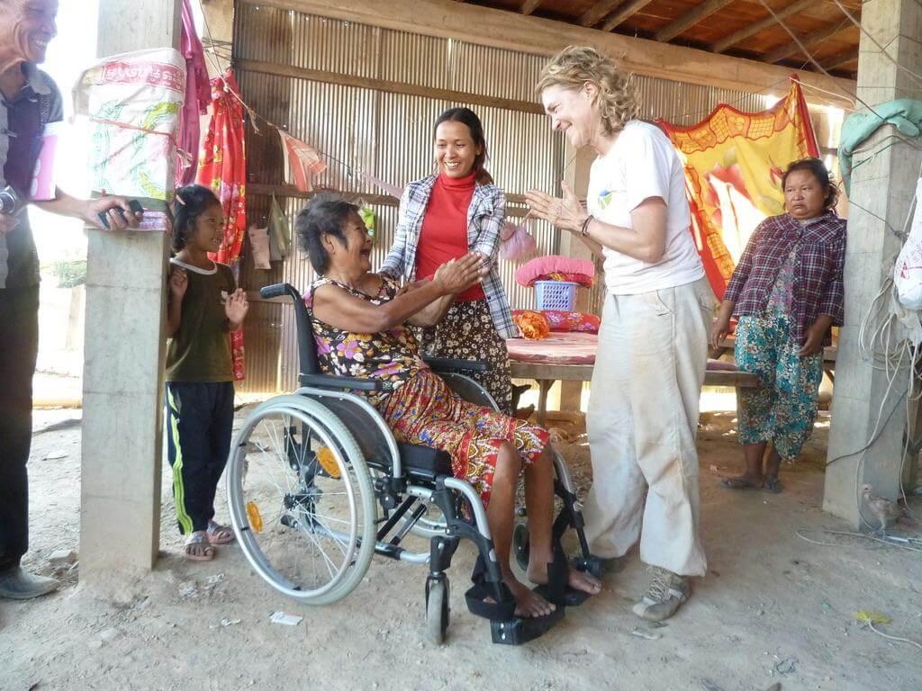 Kambodschanische Frau im Rollstuhl lacht Doerte an.