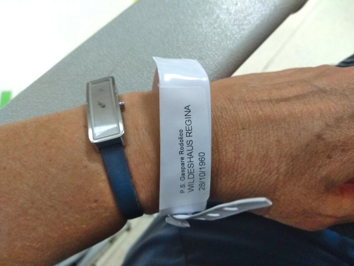 Hand mit Armbanduhr und Patientenarmband.