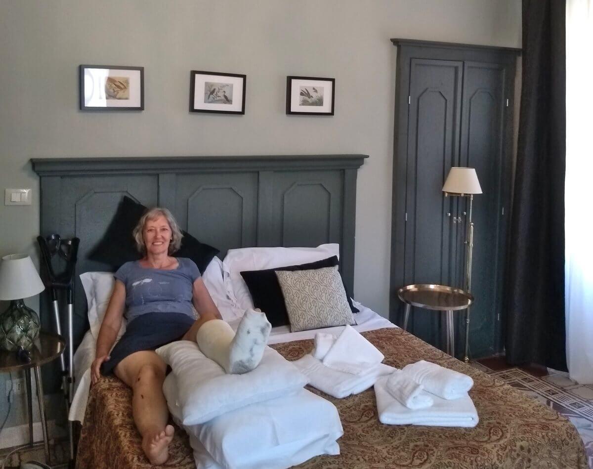 Gina mit hochgelagertem Bein in Zimmer mit Holzmöbeln.