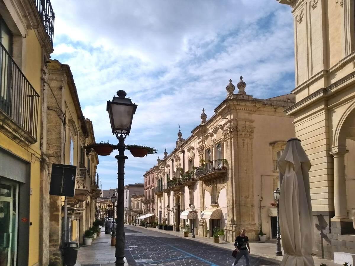 Straße mit barocken Häusern und Laterne im Vordergrund.