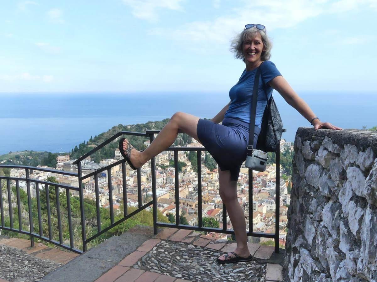 Gina hampelt auf einem Bein am Aussichtspunkt über Taormina.