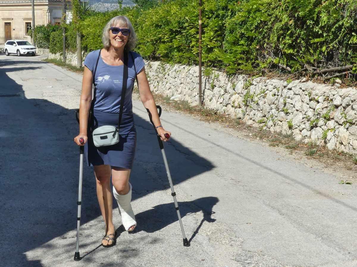 Gina mit Gipsbein und zwei Krücken auf einer Straße.