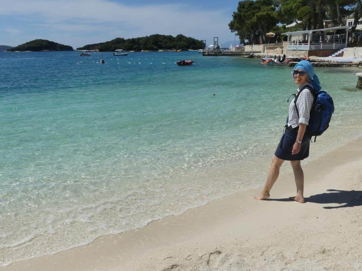 Gina steht am Strand mit türkisblauem Wasser.