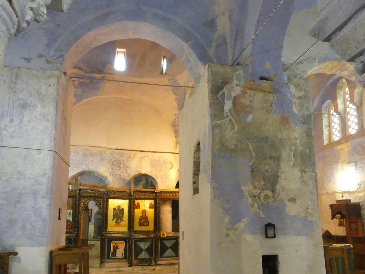 Innere der Kirche mit hellblauen Bögen und Ikonen im Hintergrund.