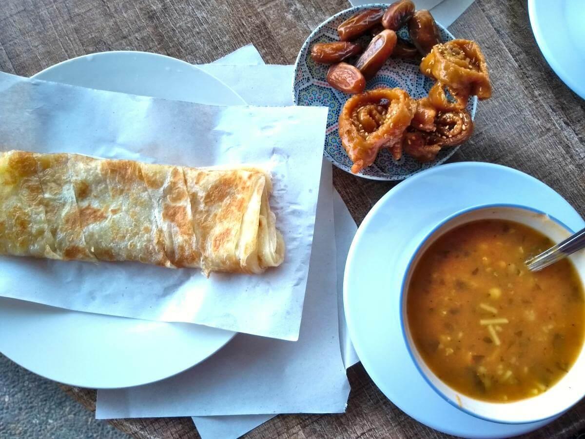 Blick von oben auf Suppenschale, Teller mit Pfannkuchen und süßes Gebäck.
