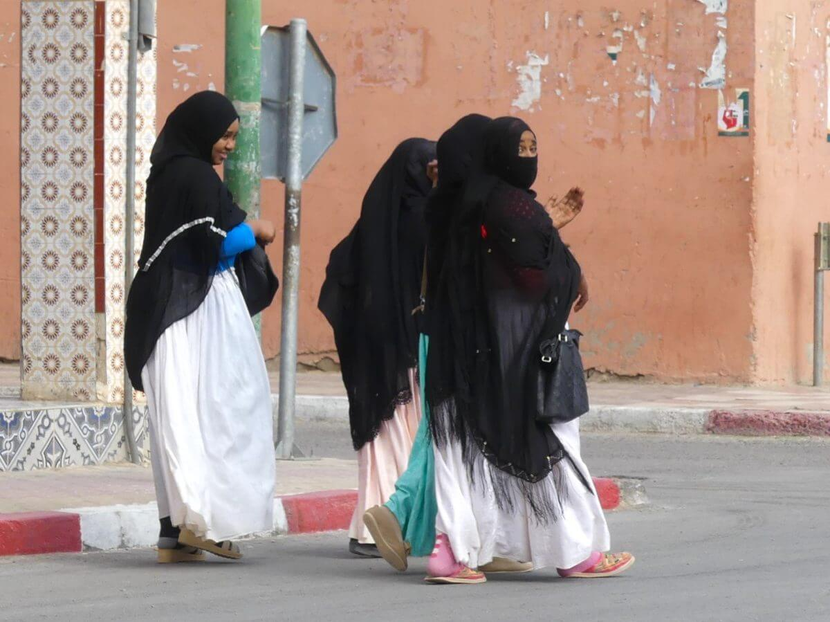 Drei Mädchen mit langen weißen Röcken und schwarzen Kopftüchern gehen über die Straße in Marokko.