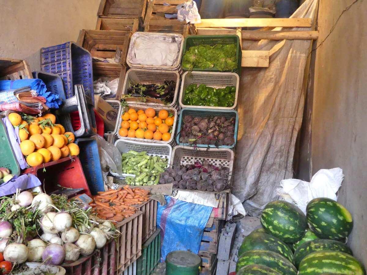 Kleiner Laden mit Kästen voller Gemüse, hoch an der Wand gestapelt.