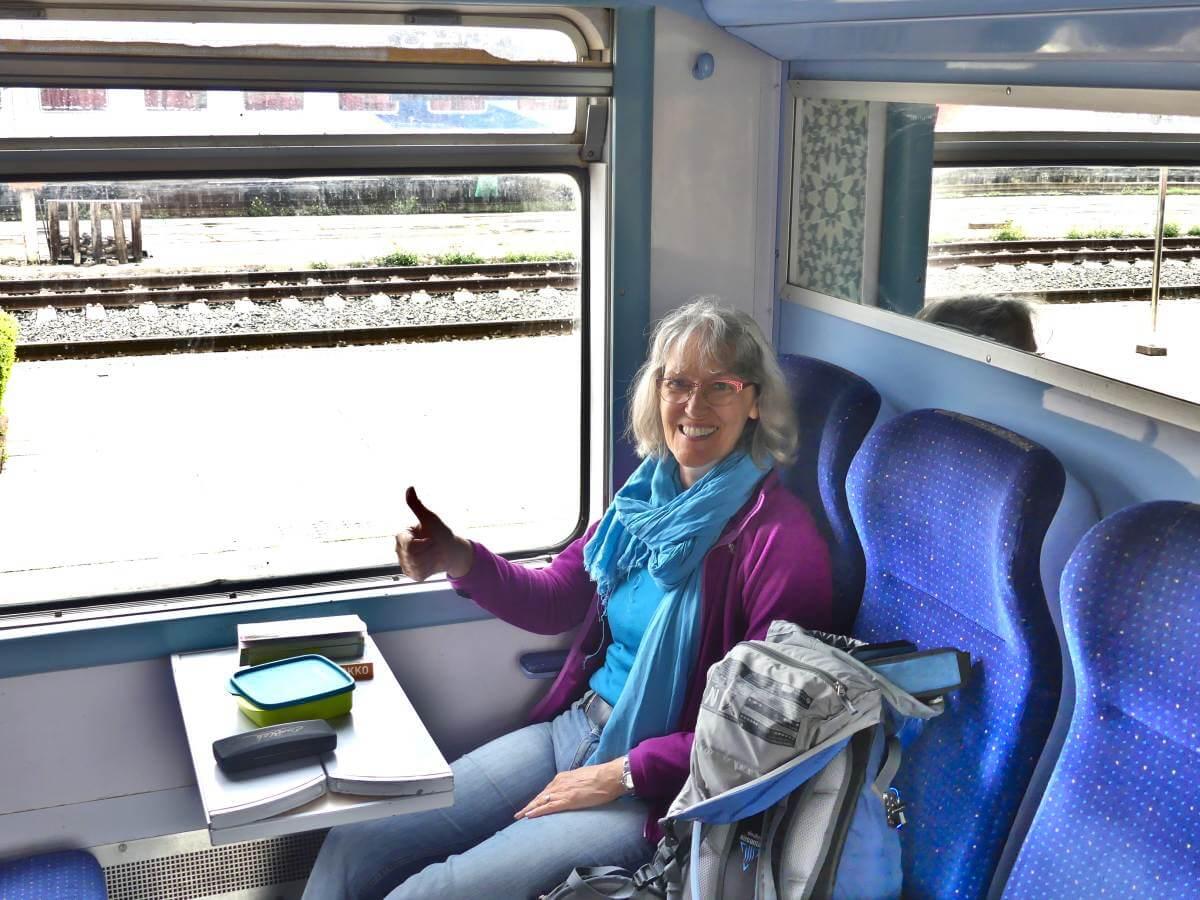 Gina sitzt im Zugabteil.