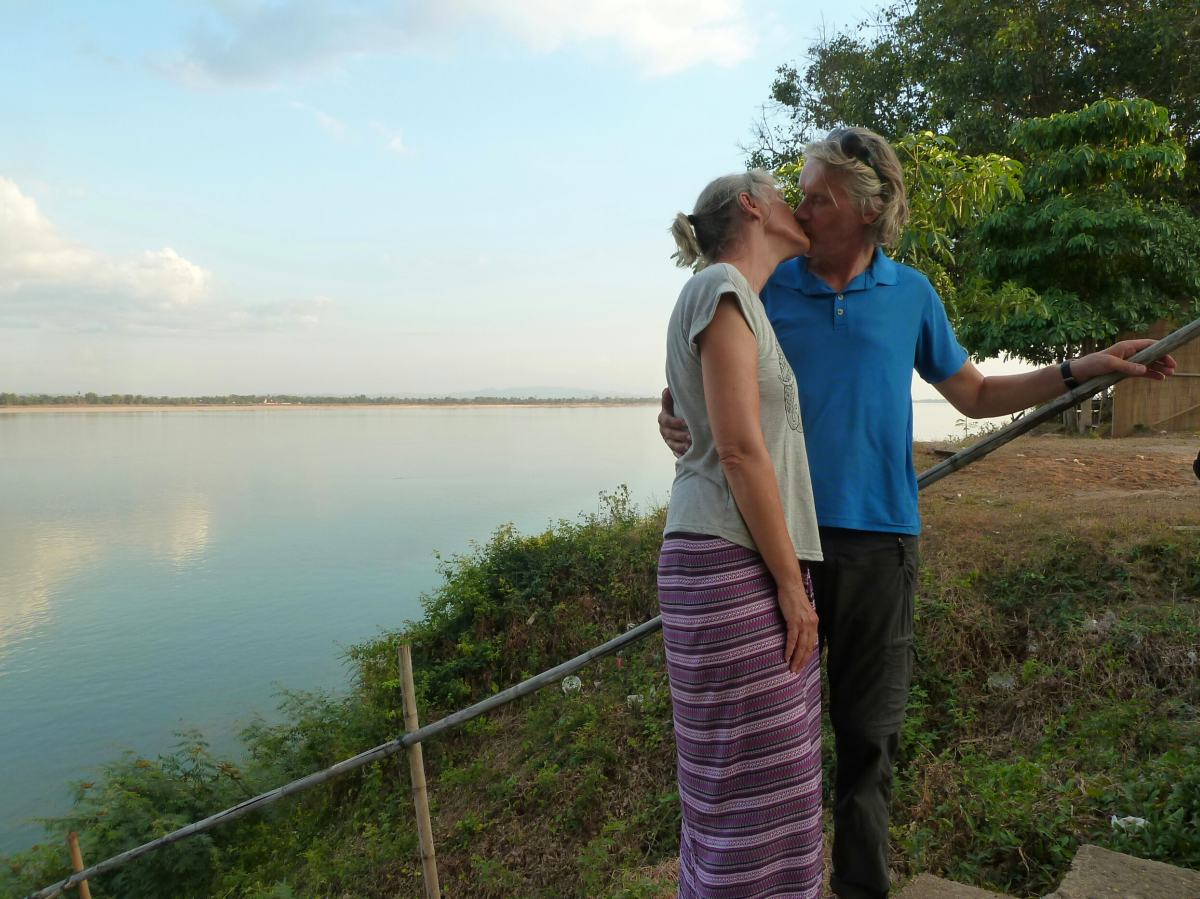 Gina und Marcus küssen sich am Ufer des breiten Flusses.