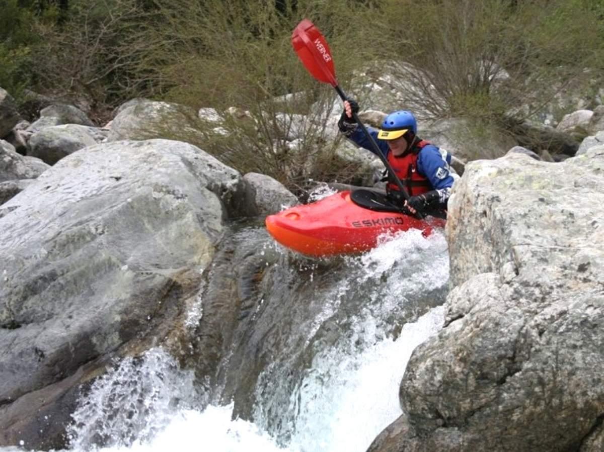 Paddler fährt über Kante eines Wasserfalls.