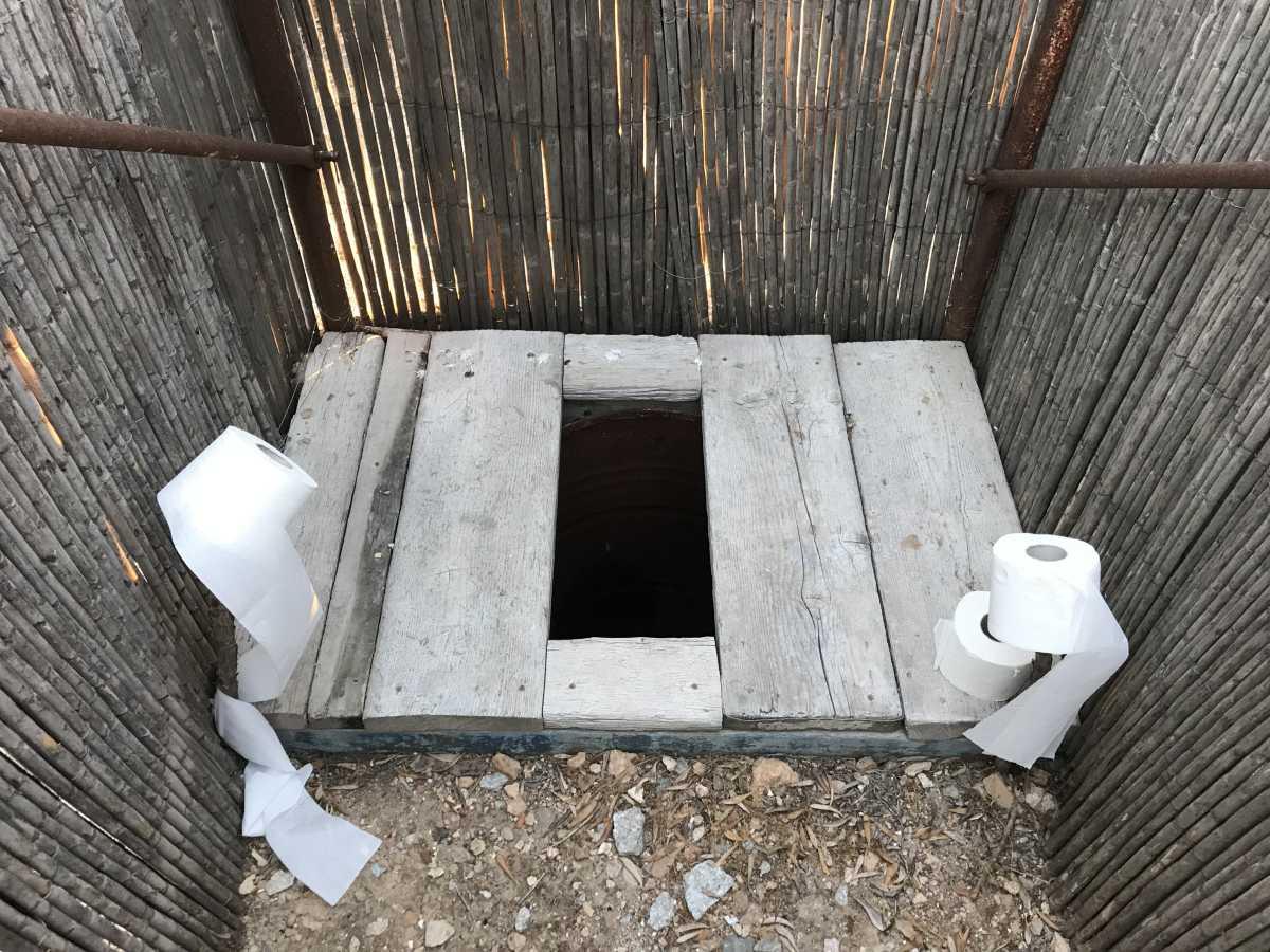 Holzbretter mit Lücke dazwischen als Toilette.