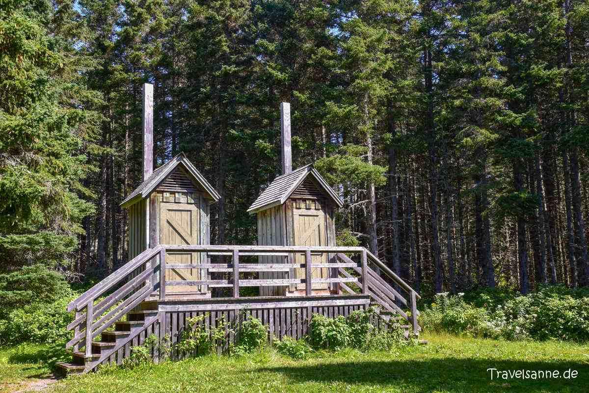 2 hölzerne Toiletten-Häuschen am Waldrand,