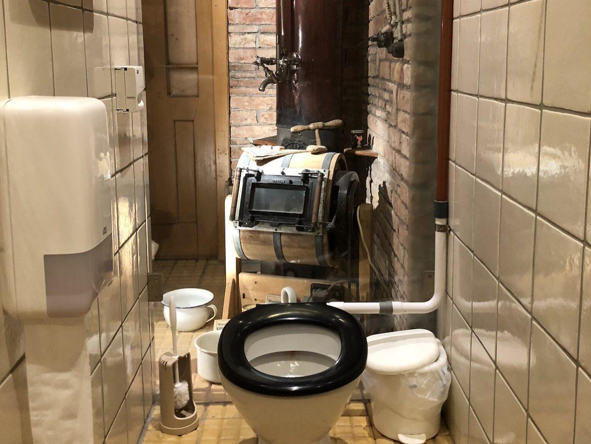 Toilette vor Glaswand zur Ausstellung.