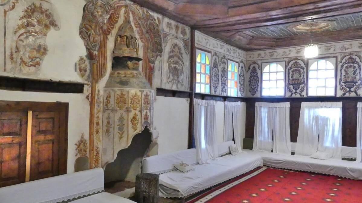 Raum mit rotem Teppich, Diwanen und Fresken an den Wänden.
