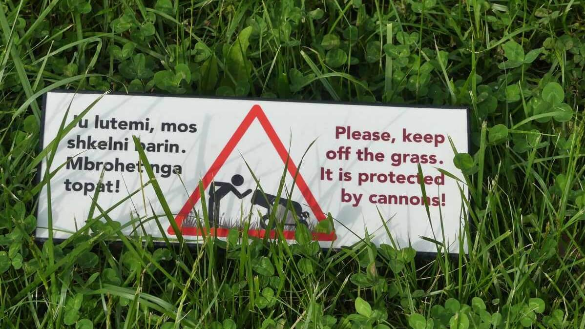 Schild mit Text Please keep off the grass. It is protected by cannons.