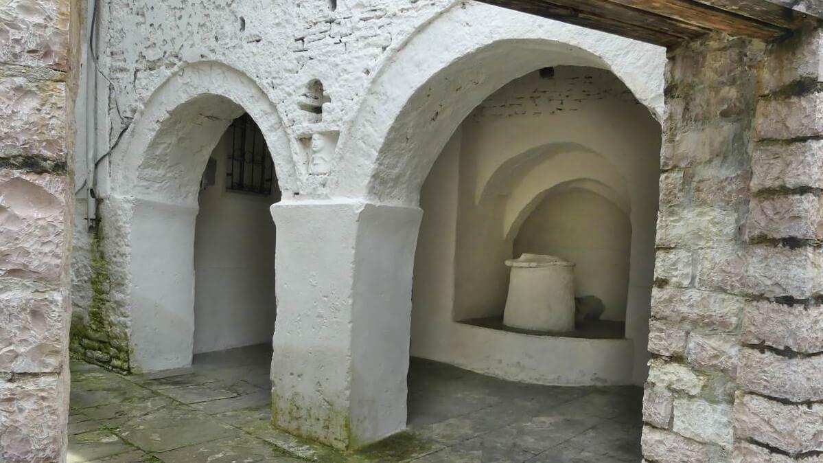 Rundbögen mit Brunnen in Nische.