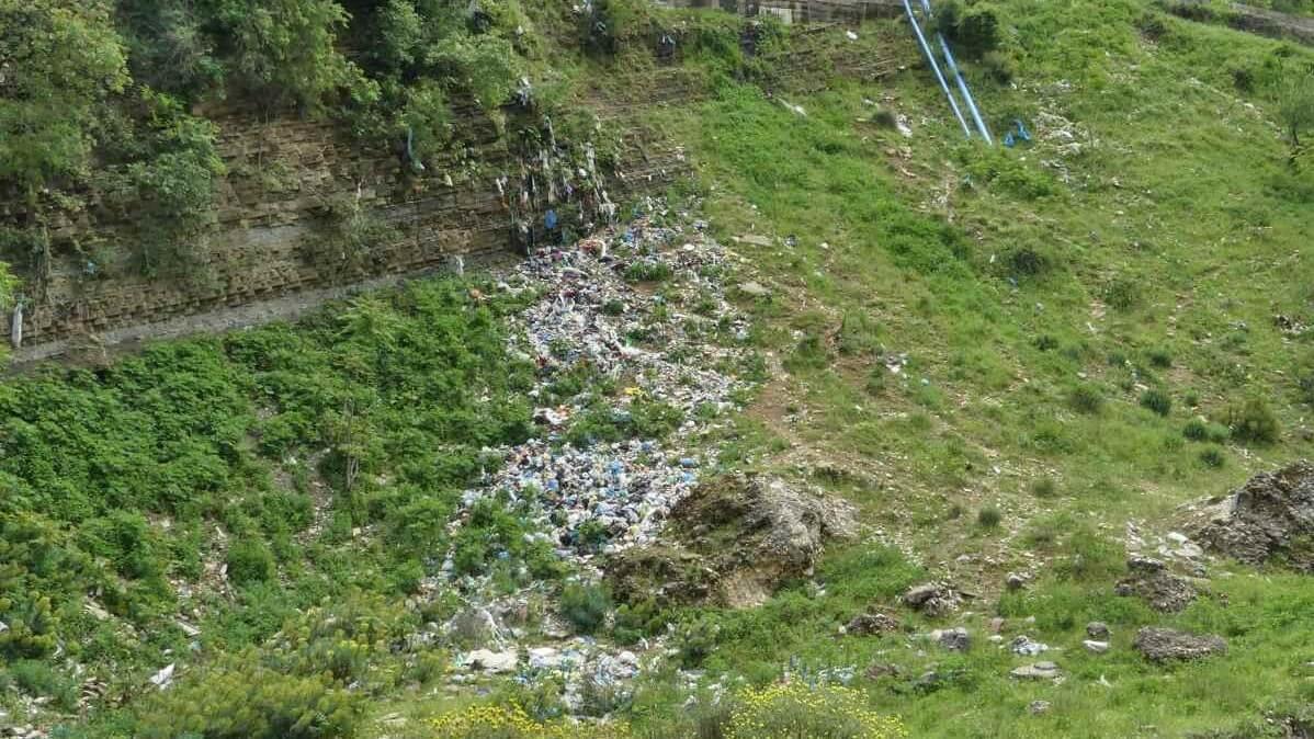 Müll liegt verstreut einen steilen Abhang hinunter.