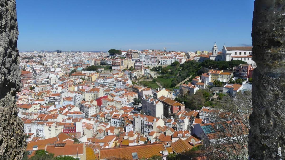 Blick durch die Zinnen der Burgmauer auf die Dächer von Lissabon.
