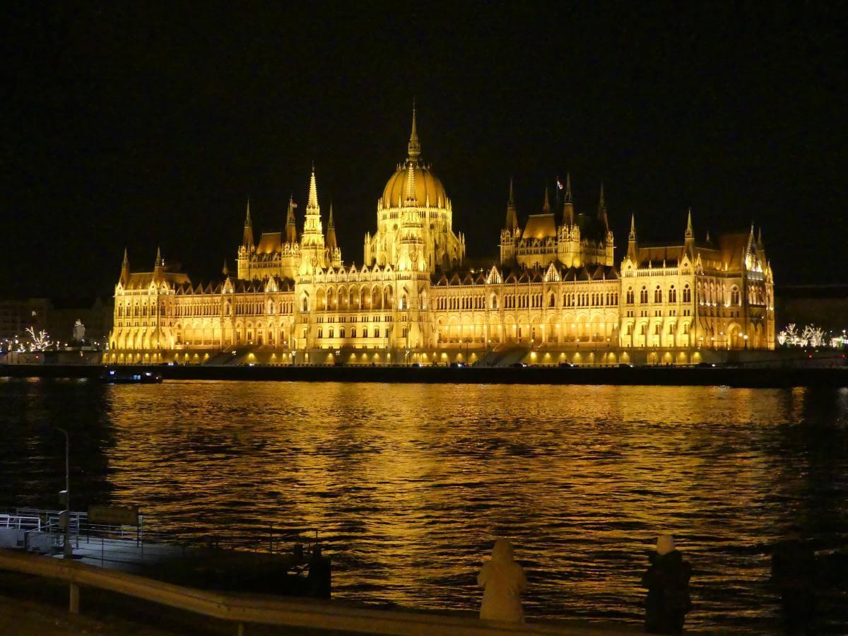 Beleuchtetes Parlamentsgebäude am Donauufer.