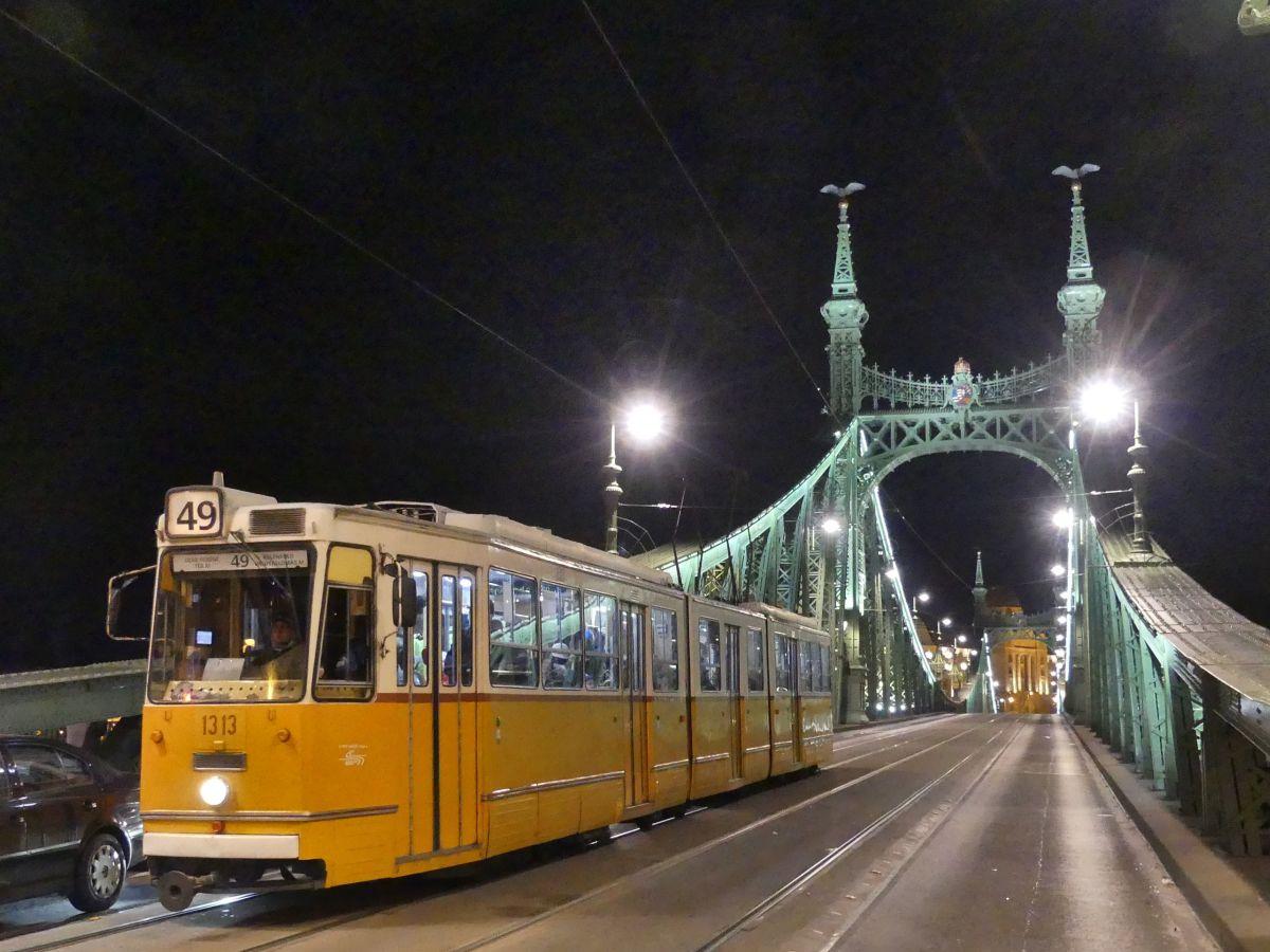Gelbe Straßenbahn bei Nacht.