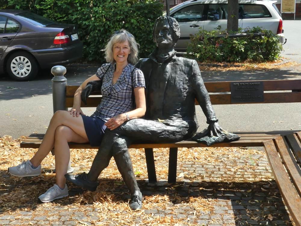 Gina sitzt neben der Goethe-Skulptur auf der Bank.