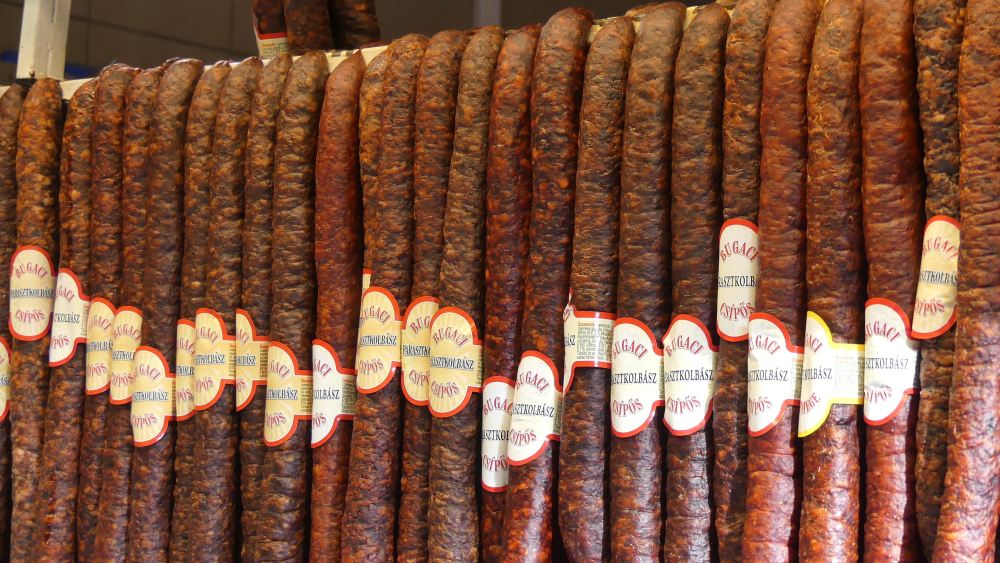 Eine dichte Reihe von Salamis hängt am Marktstand.
