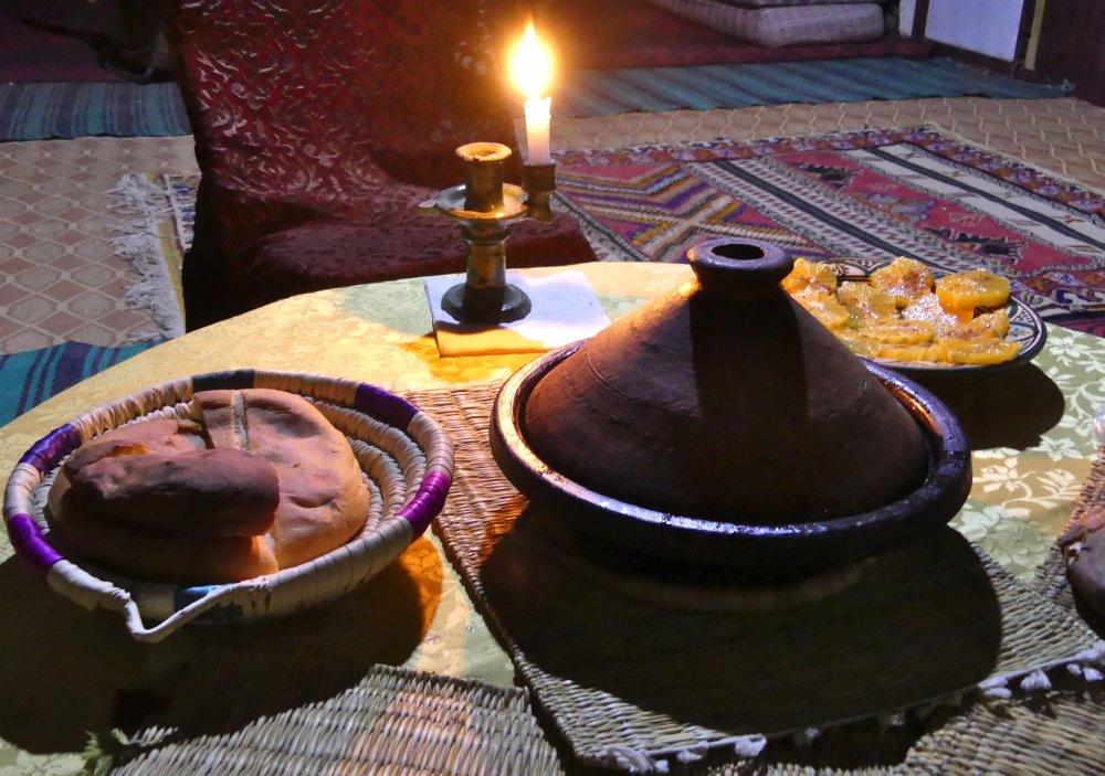 Tisch mit Tajine, Brotkorb und Kerze.