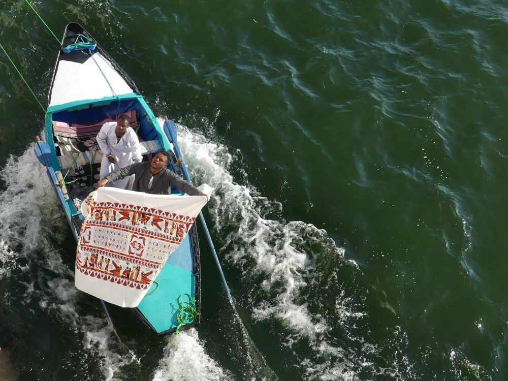 Händler präsentiert seine Ware auf dem Boot.