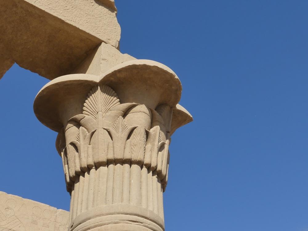 Säulenkapitell vor blauem Himmel.