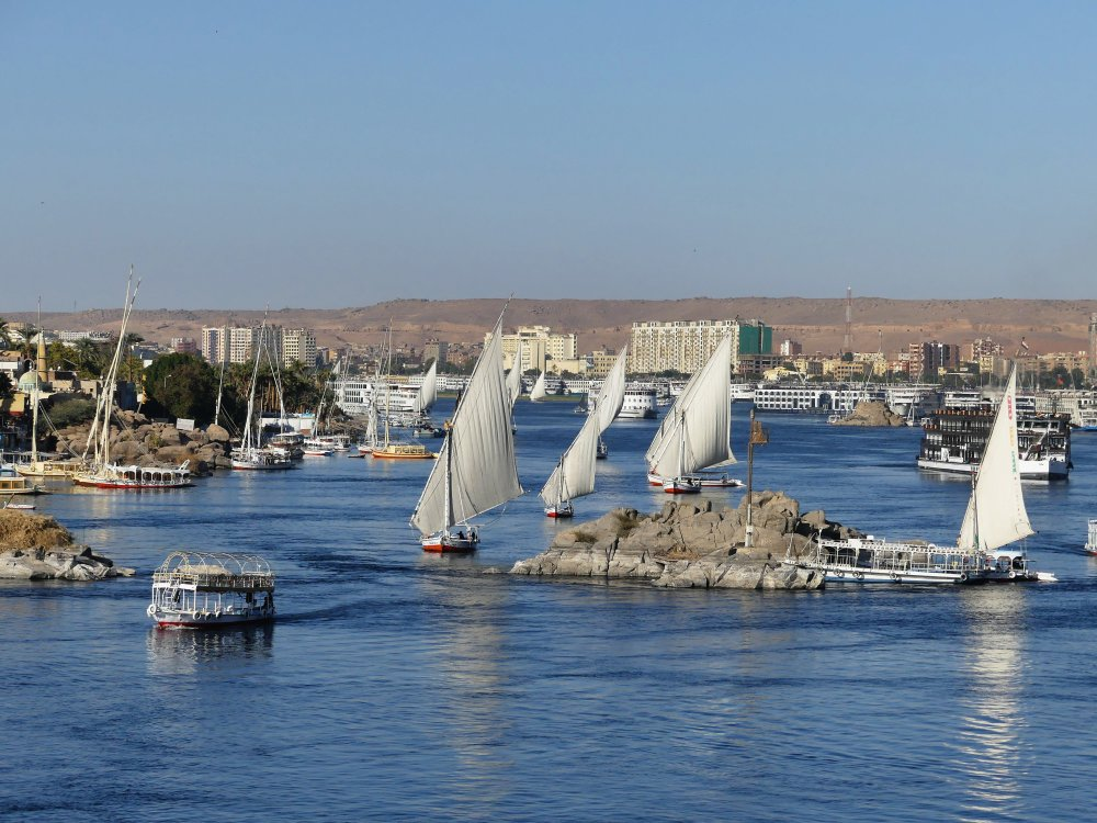 Mehrere Feluken segeln zwischen Felsklippen auf dem Nil.