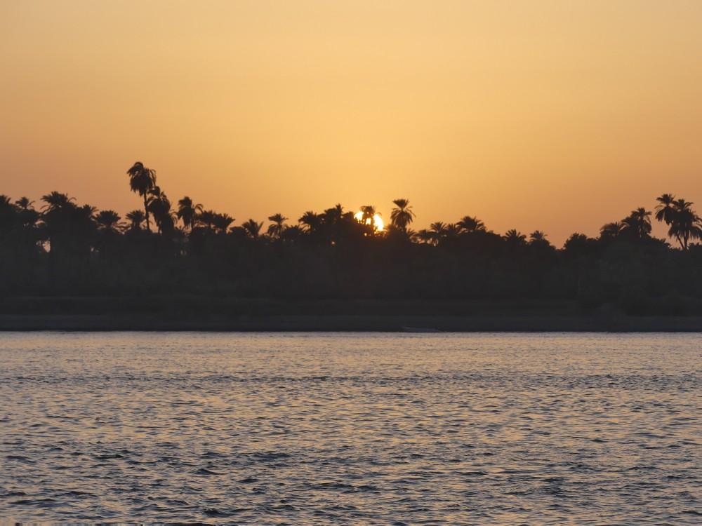 Die Sonne geht hinter dem Ufer unter.