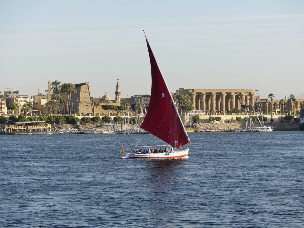 Eine Feluke mit rotem Segel fährt auf dem Nil.
