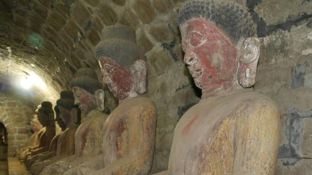 Buddha-Statuen in einem dunklen Gang.