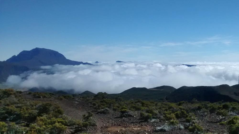 Berggipfel ragt aus Wolkenschicht.