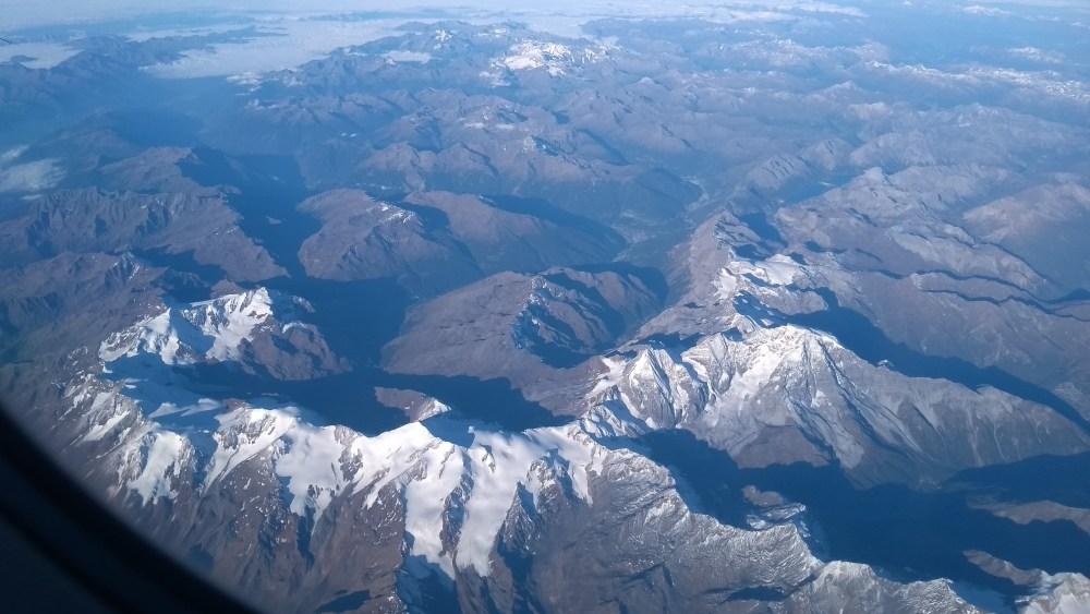 Luftaufnahme von schneebedeckten Gipfeln der Alpen.