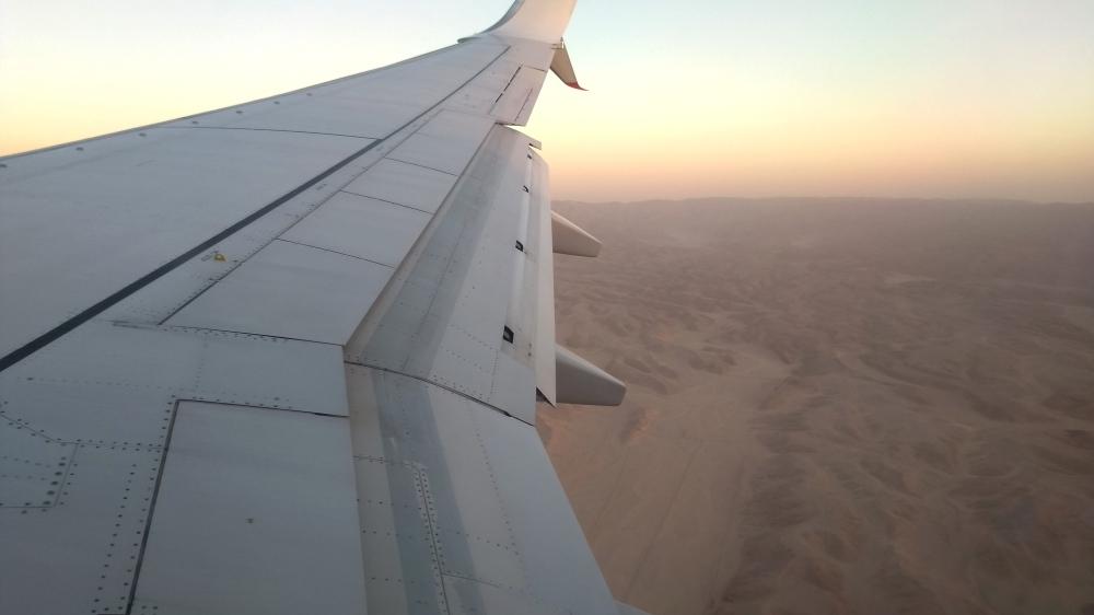 Flugzeugflügel und Wüste.