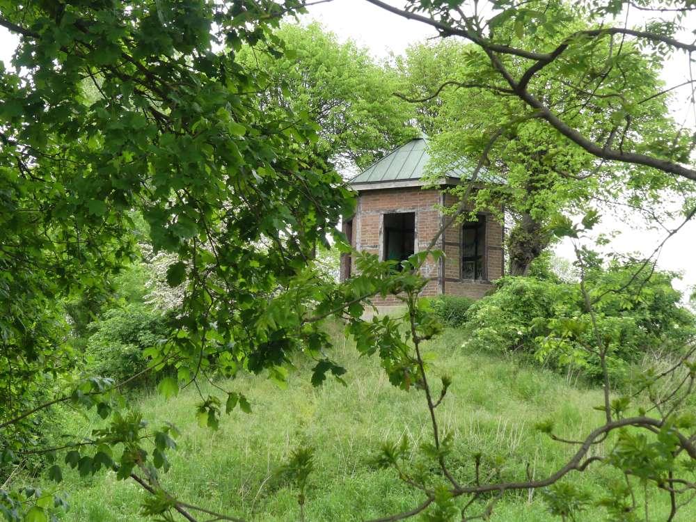 Pavillon auf einem grünen Hügel.