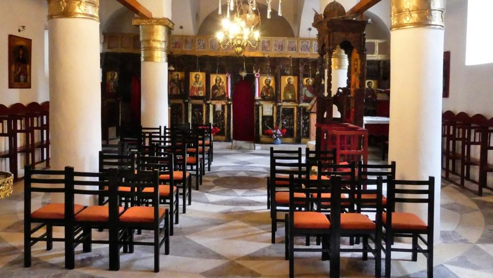 Innenraum der Kirche mit weißen Säulen und dunklem Holzschnitzwerk.