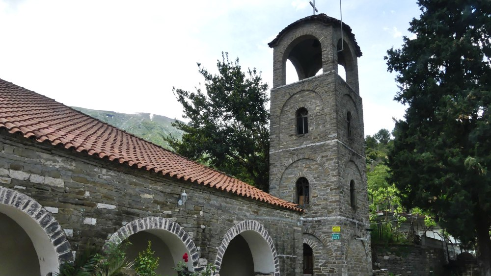Orthodoxe Kirche mit Turm und Steinbögen.
