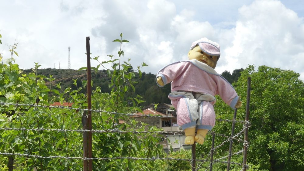 Eine Puppe hängt an einem Zaun.
