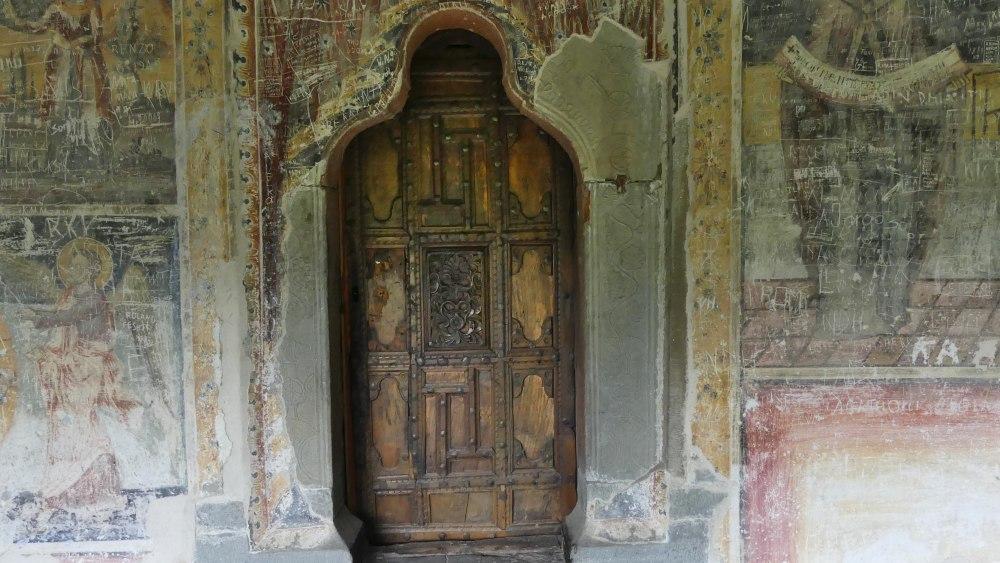 Alte Holztür und verblichene Fresken.