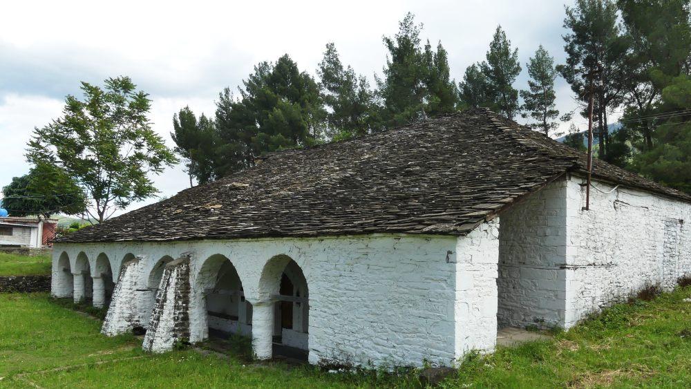 Niedriges weißes Kirchengebäude.
