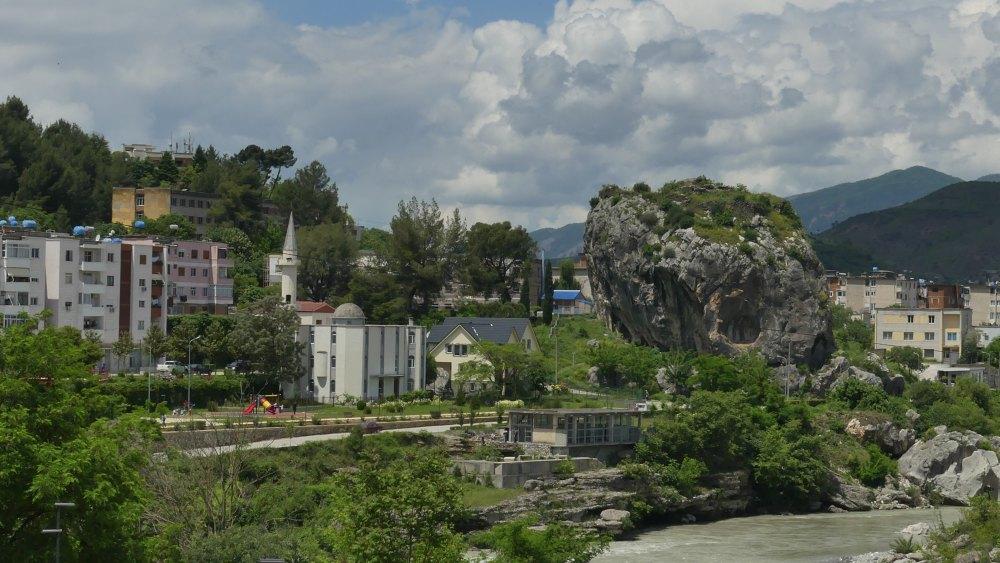 Stadtansicht von Permet mit Fluss und großem Felsen.