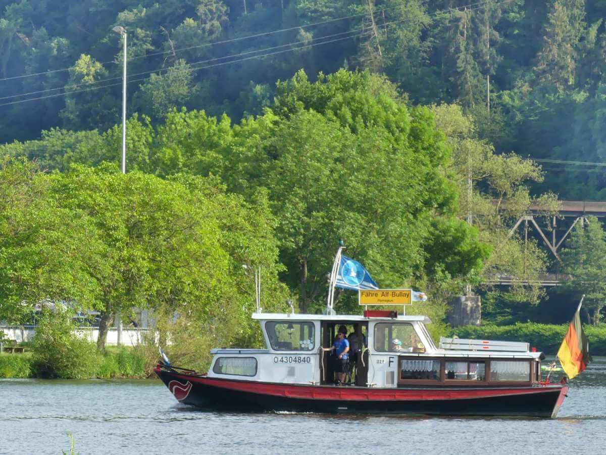 Schiff mit schwarzem Rumpf und weißen Aufbauten fährt über die Mosel.