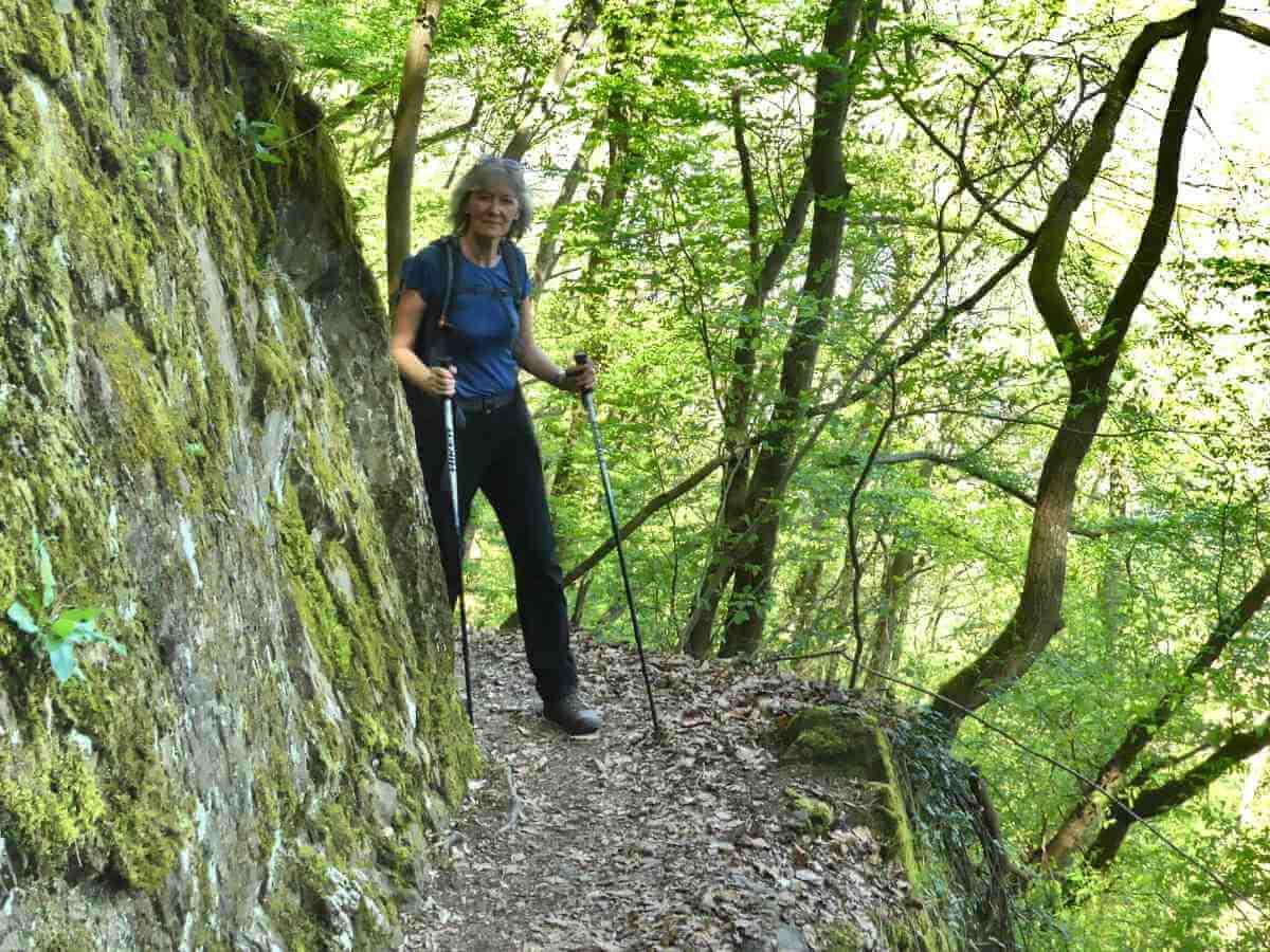 Gina kommt auf einem schmalen Weg um eine Felskante gelaufen in der Briederner Schweiz.
