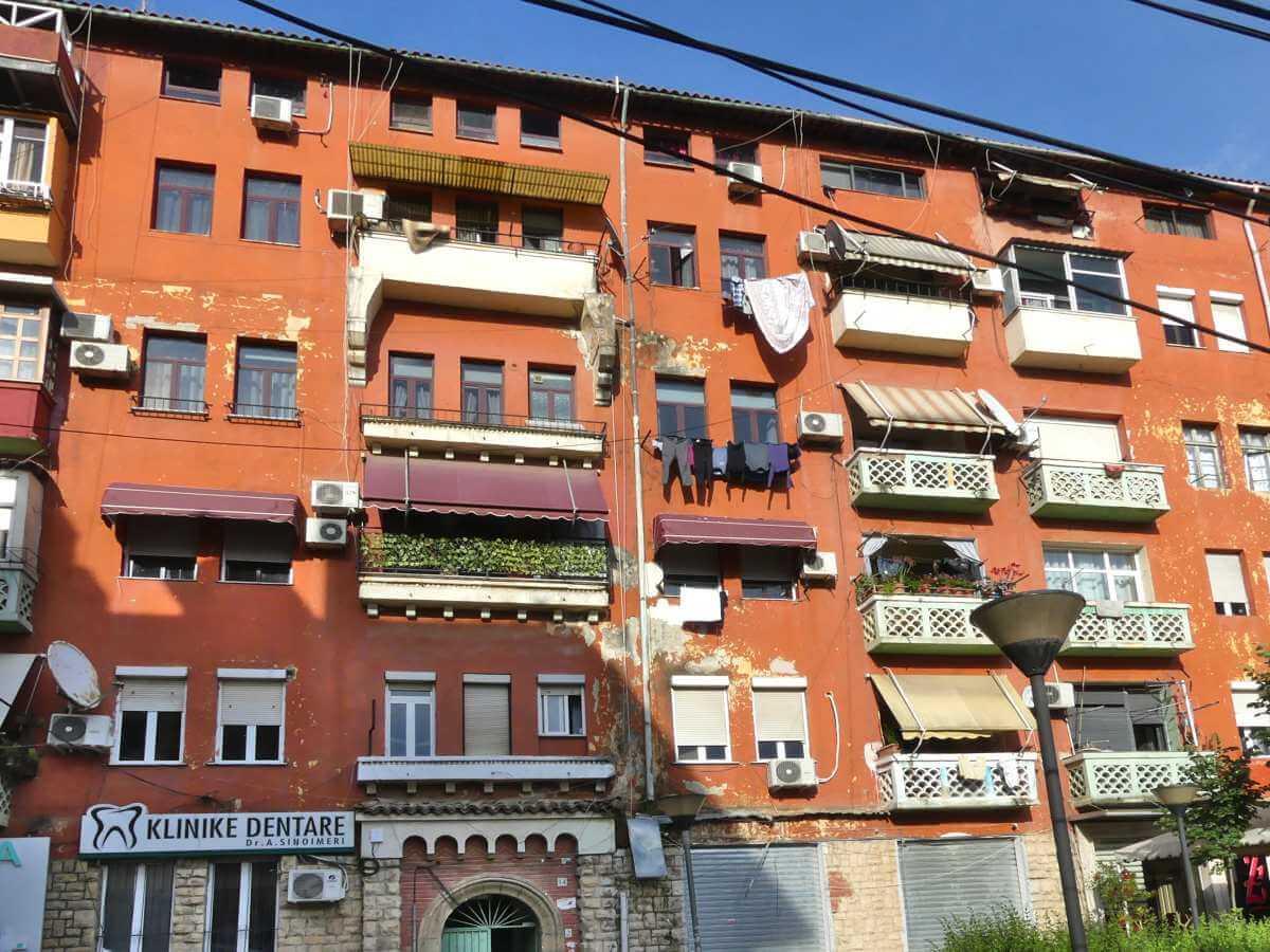 Fassade eines großen fünfstöckigen Hauses in Tirana, vor den Fenstern hängt Wäsche.