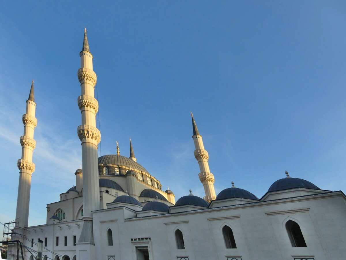 Moschee mit großem Kuppelbau und vier schlanken Minaretten vor blauem Himmel.