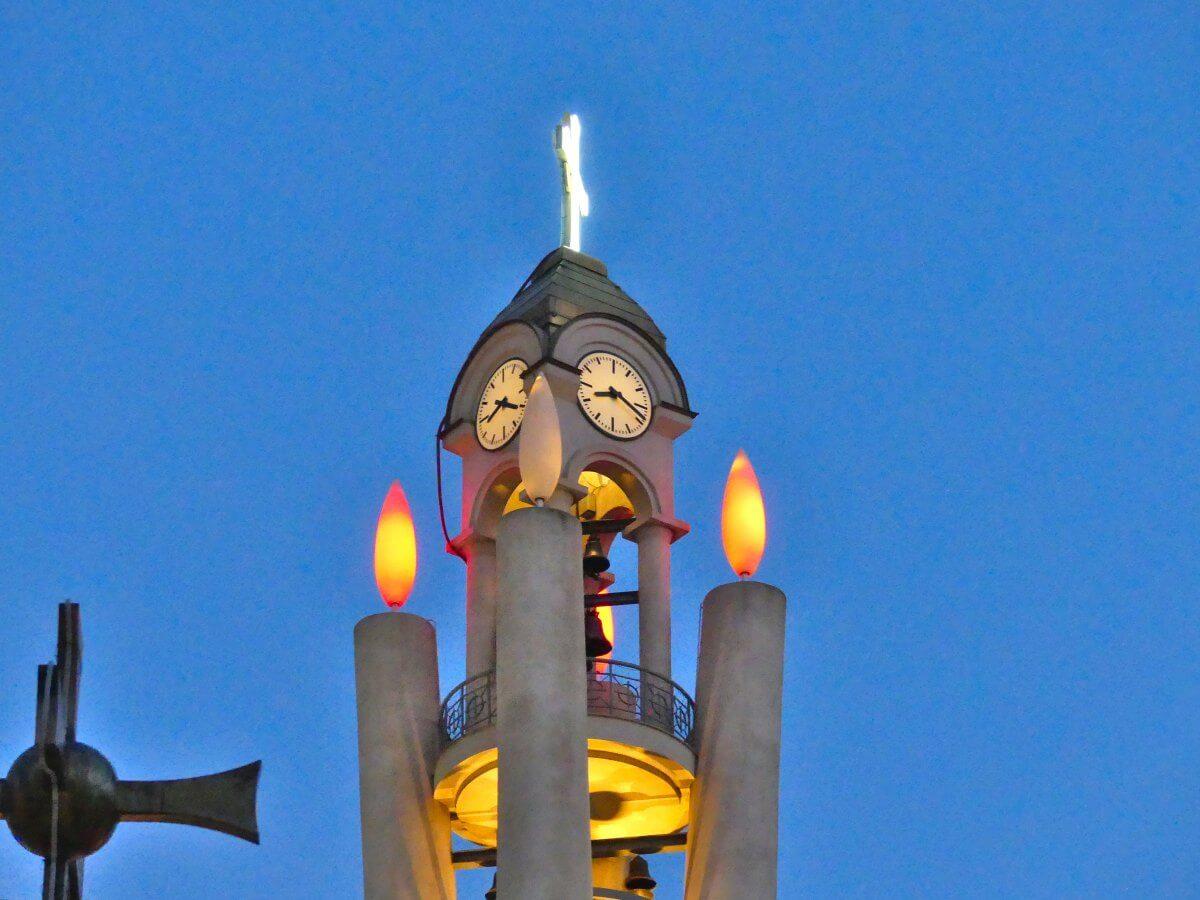 Moderner Betonturm mit Uhr und vier stilisierten, leuchtenden Kerzen.