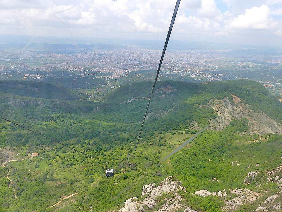 Blick aus der Höhe über steile grüne Hänge und den Talkessel von Tirana.